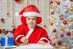 Mädchen gekleidet als Santa Claus-Schreiben auf einem Blatt Papier sitzend am Tisch Lizenzfreie Stockfotografie