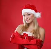 Mädchen gekleidet als Weihnachtsmann auf einem roten Hintergrund Lizenzfreie Stockbilder