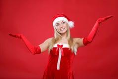 Mädchen gekleidet als Weihnachtsmann auf einem roten Hintergrund Stockfoto