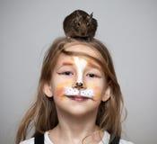 Mädchen gemalt als Katze mit grauer Maus auf dem Kopf Stockfotografie