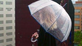 Mädchen genießt Regen auf der Dachspitze ihres Hauses stock footage