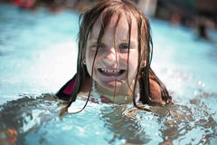 Mädchen genießt Sommertag am Swimmingpool. Lizenzfreie Stockfotografie