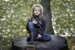 Mädchen gesetzt auf einem Stamm im Park Lizenzfreie Stockfotografie