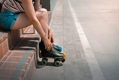 Mädchen gesetzt an der Treppe, die Rollschuhe bei Venice Beach, Los Angeles, Kalifornien, USA bindet lizenzfreie stockfotografie