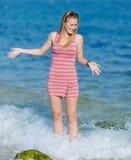 Mädchen in gestreiftem Kleid steht im Wasser und lacht Stockfoto