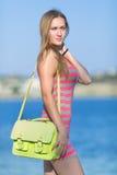 Mädchen in gestreiftem Kleid und gelbe Tasche auf Strand Lizenzfreies Stockbild