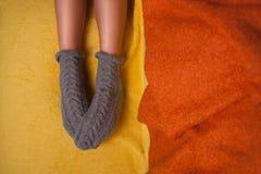 Mädchen in gestrickten Socken auf dem Sofa Stockfotografie