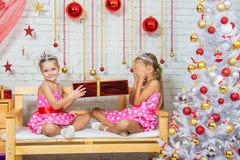 Mädchen gibt einem anderen Mädchen ein Geschenk, das auf einer Bank in einer Weihnachtseinstellung sitzt Stockfoto