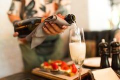 Mädchen gießt Champagner in Glas im gemütlichen Café stockbild