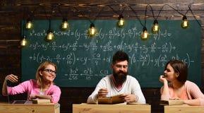 Mädchen, glückliche Studenten, die mit Verehrung bärtigem Lehrer, Lektor, Professor betrachten College und Bildungskonzept stockfotos