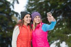 Mädchen-Griff-intelligente Telefon-Kamera, die Selfie-Foto-Schnee-Forest Young Woman Couple Outdoor-Winter nimmt Stockfotos