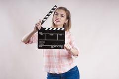 Mädchen hält ein clapperboard und eine Aufstellung Produzentanfang auf weißem Hintergrund lizenzfreie stockfotos