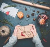 Mädchen hält ein Geschenk für ein neues Jahr oder ein Weihnachten, ein Umschlag, eine Glühweinschale, Packpapier, Weihnachtsbäume lizenzfreies stockfoto
