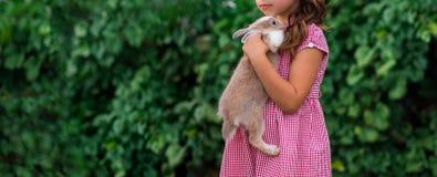 Mädchen hält ein nettes Kaninchen, Trieb im Freien stockbild