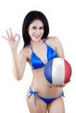 Mädchen hält einen Ball und zeigt perfektes Zeichen Stockbild