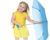 Mädchen hält einen blauen Regenschirm in ihren Händen Stockfoto