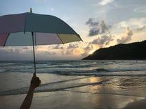 Mädchen hält einen bunten Pastellregenschirm auf dem Strand mit überraschendem Sonnenuntergang stockbild
