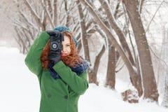 Mädchen hält Fotografien durch Retro- Kamera am Wintertag Lizenzfreies Stockfoto