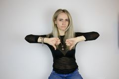 Mädchen hält ihre Finger nach unten und zeigt die Hoffnungslosigkeit der Situation lizenzfreie stockbilder
