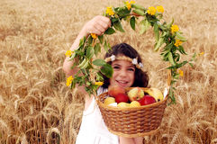 Mädchen hält Korb der Frucht auf dem Gebiet des Weizens an Stockfoto