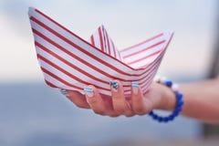 Mädchen hält Weißbuchschiff mit roten Linien auf ihrer Hand Lizenzfreies Stockbild