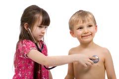 Mädchen hört mit einem Stethoskop Lizenzfreie Stockbilder