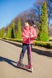 Mädchen haben Spaß auf dem Roller im warmen Frühlingstag Stockfotografie