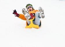 Mädchen hat Spaß, indem sie hinunter den schneebedeckten Hügel sledging Stockfoto
