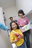 Mädchen-helfende Eltern in den Hausarbeiten stockfoto