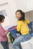 Mädchen-helfende Mutter in waschender Kleidung stockfotografie