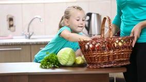 Mädchen hilft ihrer Mutter, die Gemüse vom Korb zieht stock video footage