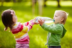 Mädchen hilft Jungen, Flasche zu halten Stockbild