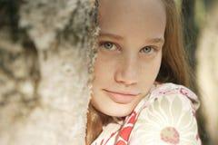 Mädchen hinter Baum Stockfoto