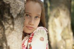 Mädchen hinter Baum im Wald Stockbilder