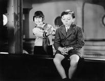 Mädchen hinter einem Jungen, der vortäuscht, ihn über Bord zu drücken (alle dargestellten Personen sind nicht längeres lebendes u Lizenzfreies Stockbild