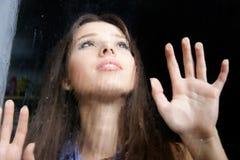Mädchen hinter nassem Fenster stockfotografie
