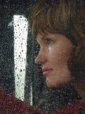 Mädchen hinter waterdropped Glas Stockbild