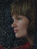 Mädchen hinter waterdropped Glas Stockbilder