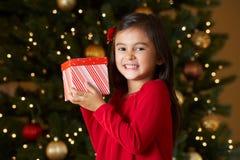 Mädchen-Holding-Weihnachtsgeschenk vor Baum Stockfotos