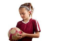 Mädchen Holidng ein Fußball, der unten schaut Lizenzfreie Stockfotos