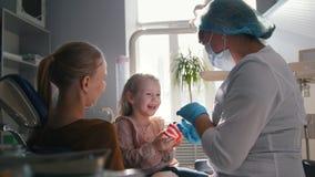Mädchen, ihre Mutter und der Zahnarzt im zahnmedizinischen Büro, das stomatologist, die neugierig überprüfen und sich beraten, Tö stock video