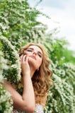 Mädchen im AbendCocktailkleid auf einem Frühling in der Mitte unter blühenden Büschen und dem schönen Lächeln der Bäume Lizenzfreies Stockbild