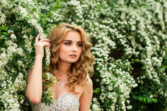 Mädchen im AbendCocktailkleid auf einem Frühling in der Mitte unter blühenden Büschen und dem schönen Lächeln der Bäume Stockfoto