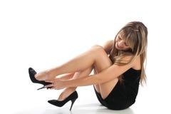 Mädchen im Abendkleid, das auf Schuhe sich setzt Stockbilder