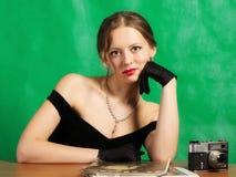Mädchen im Abendkleid, das bei Tisch mit Zeitschriften sitzt lizenzfreies stockfoto