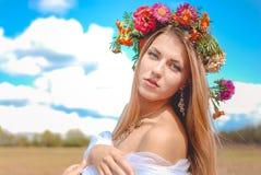 Mädchen im Asterkranz, der Kamera auf Sommer betrachtet Stockfoto