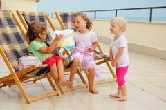 Mädchen im Aufenthaltsraum auf der Veranda, Zeichnung betrachtend lizenzfreies stockfoto