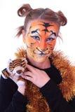 Mädchen im Aussehen ein Tiger mit einem Spielzeugtigerjungen. Stockbilder
