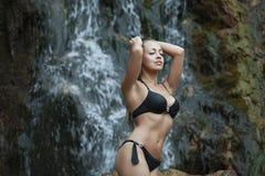 Mädchen im Badeanzug am Wasserfall lizenzfreie stockbilder