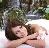 Mädchen im Badekurort gegen Wasserfall. Lizenzfreies Stockbild